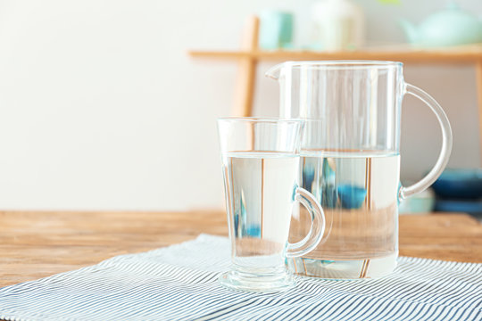 Glass cup and jug of fresh water on table indoors