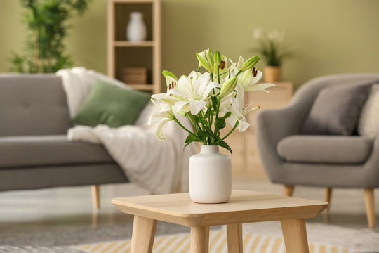 Beautiful lily flowers in vase on table in room