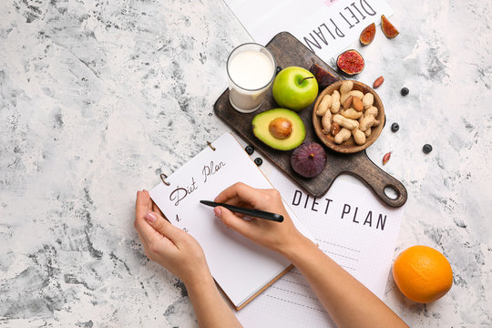Woman writing something in notebook and healthy products on white table. Diet concept