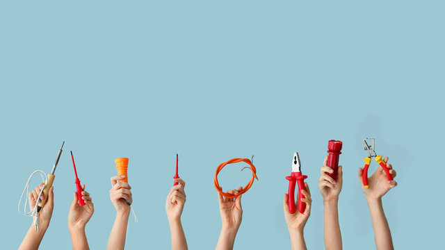 Female hands with electrician's tools on color background