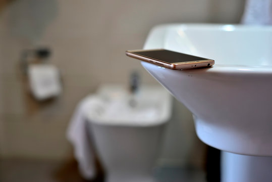 mobile phone on white washbasin and bidet defocused in the background