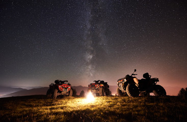 Night picture. Three atv quad motorbikes standing on the top of mountain near burning bonpfire, under amazing night starry sky and Milky way on background