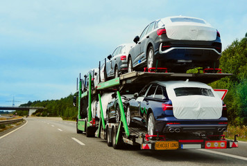 The trailer is engaged in the delivery of new cars