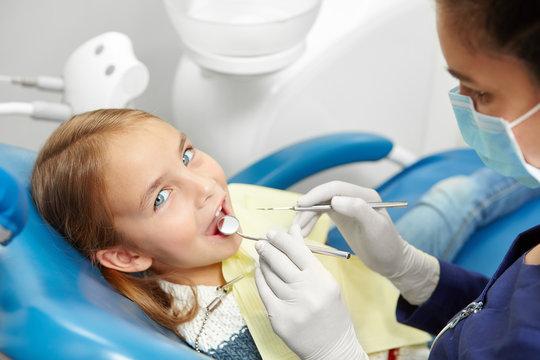 Female dentist examining little girl teeth in pediatric dentistry clinic.