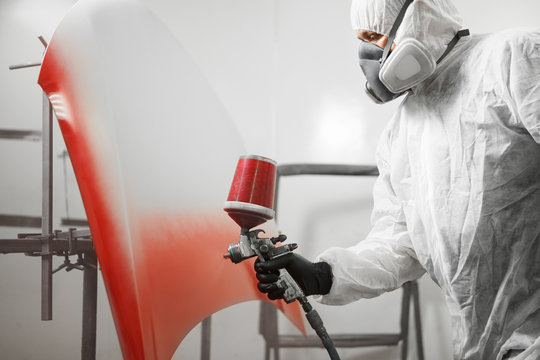 Male worker in protective clothes and mask painting hood of car using red spray paint.