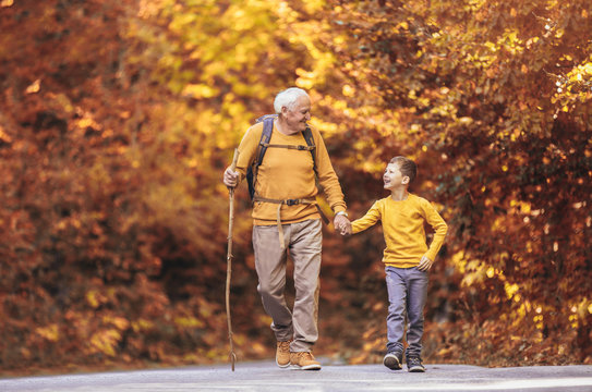 Grandfather and grandson hiking together in autumn park