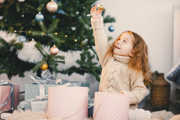 little blonde baby girl helping decorate the christmas tree by picking ornaments from a decor box and hanging them on the tree