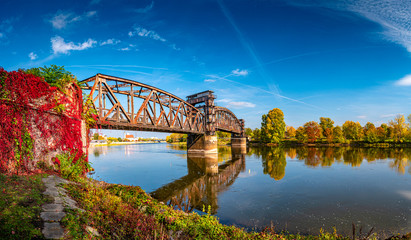 Cityscape of old railway metal rusty bridge in red ivy leaves over Elbe river in downtown of Magdeburg in Autumn colors, Germany Fototapete