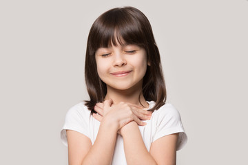 Cute little girl with hands on chest praying