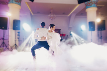 the bride and her husband dance together their first wedding dance in the restaurant