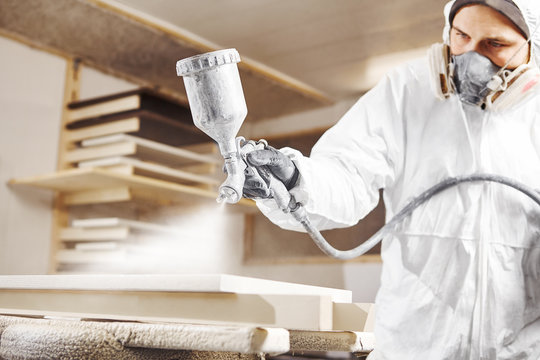 Man working with paint spray gun, airless spraying to wood
