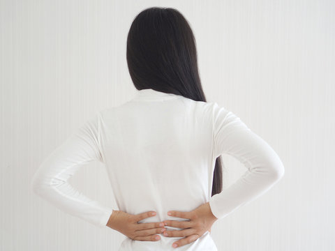herniated disc,spondylosis and scoliosis in asian woman and she touching her back cause of strains or disc injury and spinal stenosis use for health care concept.