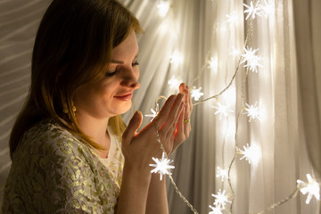 Portrait of a beautiful young white woman with brown hair holding an illuminated star shaped christmas chain of lights in her hands