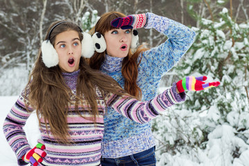 two girls in winter park/ Two surprised face, crazy winter discounts. The girls hear about crazy prices. Mommy and daughter winter. Merry mom and daughter.