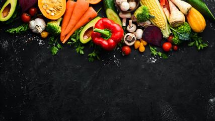 Fresh seasonal vegetables on a black stone background: Pumpkin, tomato, avocado, cucumber, onion, carrot. Autumn food. Top view. Free copy space.