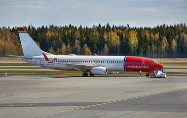 OSLO, NORWAY - MAY 3, 2015: Aircraft of Norwegian Air Shuttle taxiing at Oslo Gardermoen Airport. Pushed back by towtruck, ready for departure