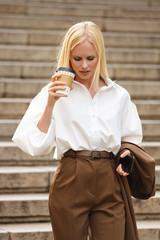 Business woman walking by steps outdoors in formalwear