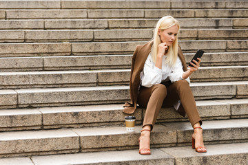 Business woman sit on steps in formalwear using mobile phone.