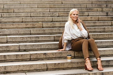 Woman sit on steps outdoors in formalwear talking by mobile phone.