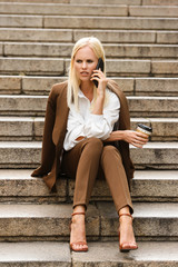 Amazing business woman sit on steps talking by mobile phone.