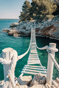 Rope bridge over a cliff in Punta Christo, Pula, Croatia - Europe. Travel photography, perfect for magazines and travel destination articles.