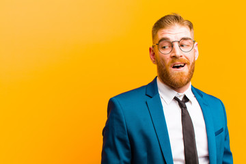 young red head businessman feeling shocked, happy, amazed and surprised, looking to the side with open mouth against orange background
