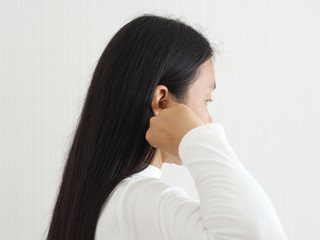 itchy ear in asian woman causes of otitis externa and hearing aid use and psoriasis use for health care concept.