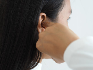 itchy ear in asian woman causes of otitis externa and hearing aid use and psoriasis use for health care concept.., closeup shot photo.