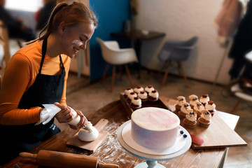 cheerful smiling woman gets pleasure form decorating cup cakes. close up side view photo