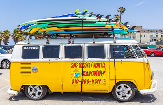 Surf boards stacked on a yellow van roof, sunny spring day. Venice beach, California USA.