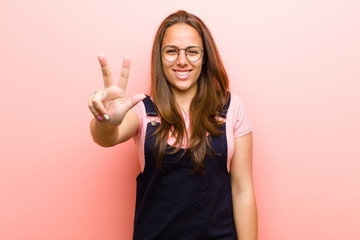young  woman smiling and looking friendly, showing number three or third with hand forward, counting down against pink background