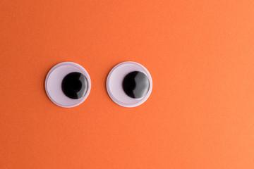 Googly eyes on orange background. Minimal holiday concept.