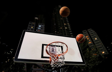 Protester throw basketballs at a hoop with NBA star LeBron James' photo during a gathering in support of NBA's Houston Rockets' team general manager Daryl Morey, who sent a tweet backing the pro-democracy movement, in Hong Kong