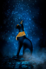 Dark night magic scene. Egyptian goddess Bastet, a statuette of a black Egyptian cat on a background of an old cobblestone road. Blue neon, moonlight at night.