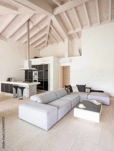 Modern living room with low sofa and white and black kitchen ...