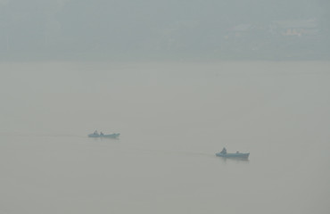 Fishermen travel on wooden boats as smog covers Batanghari river due to the forest fires in Jambi