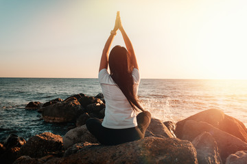 The concept of yoga and outdoor sports. Young woman doing yoga sitting on a large stone. In the background, a rocky shore, sea and surf. Sunset light. Rear view. Copy space