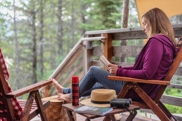 woman sitting outside cabin in woods relaxing with a book