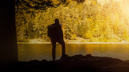 Silhouette hiker at autumnal lake