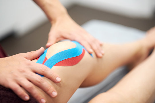 Sports injury kinesio treatment. therapist placing kinesio tape on patient's knee