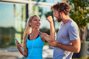 Modern woman and man jogging / exercising in urban surroundings and using cellphone at a pause /...