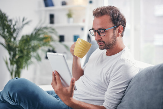 Man holding tablet, surfing online and drinking coffee.