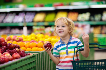 Child in supermarket. Kid grocery shopping.