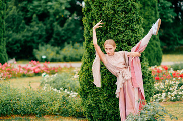 Young ballerina in theatrical dress posing with elegance at nature in italian garden