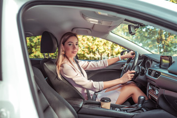 woman wheel of car machine. In summer autumn city. Business lady driving. Background trees. Beautiful girl everyday makeup. Business class sedan. Car sharing in city car rental.