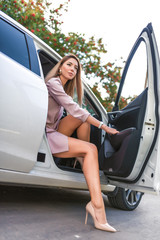 woman gets out of car in summer in autumn in city. Taxi business class. Pink suit high-heeled shoes. Tanned and slender girl with long hair. Business is an important meeting.