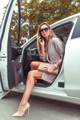 woman gets out car summer autumn city. Taxi business class. In hand mobile phone, car sharing rental, pink suit high-heeled shoes. Tanned slender girl with long hair. Business important meeting.