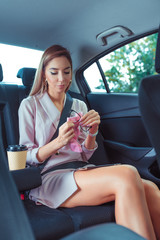Business woman in car taxi cab, pink tanned leather suit, wipes glasses with a napkin. Strict guest lady business, cup of coffee tea, trip to an important meeting.