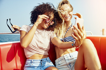 Two smiling young female friends taking selfies on a boat