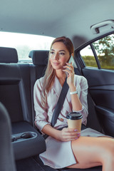 Business woman in car taxi, pink tanned leather suit, ringing on cell phone, meeting friends, renting car sharing car. Strict guest lady business, cup of coffee tea, trip to an important meeting.